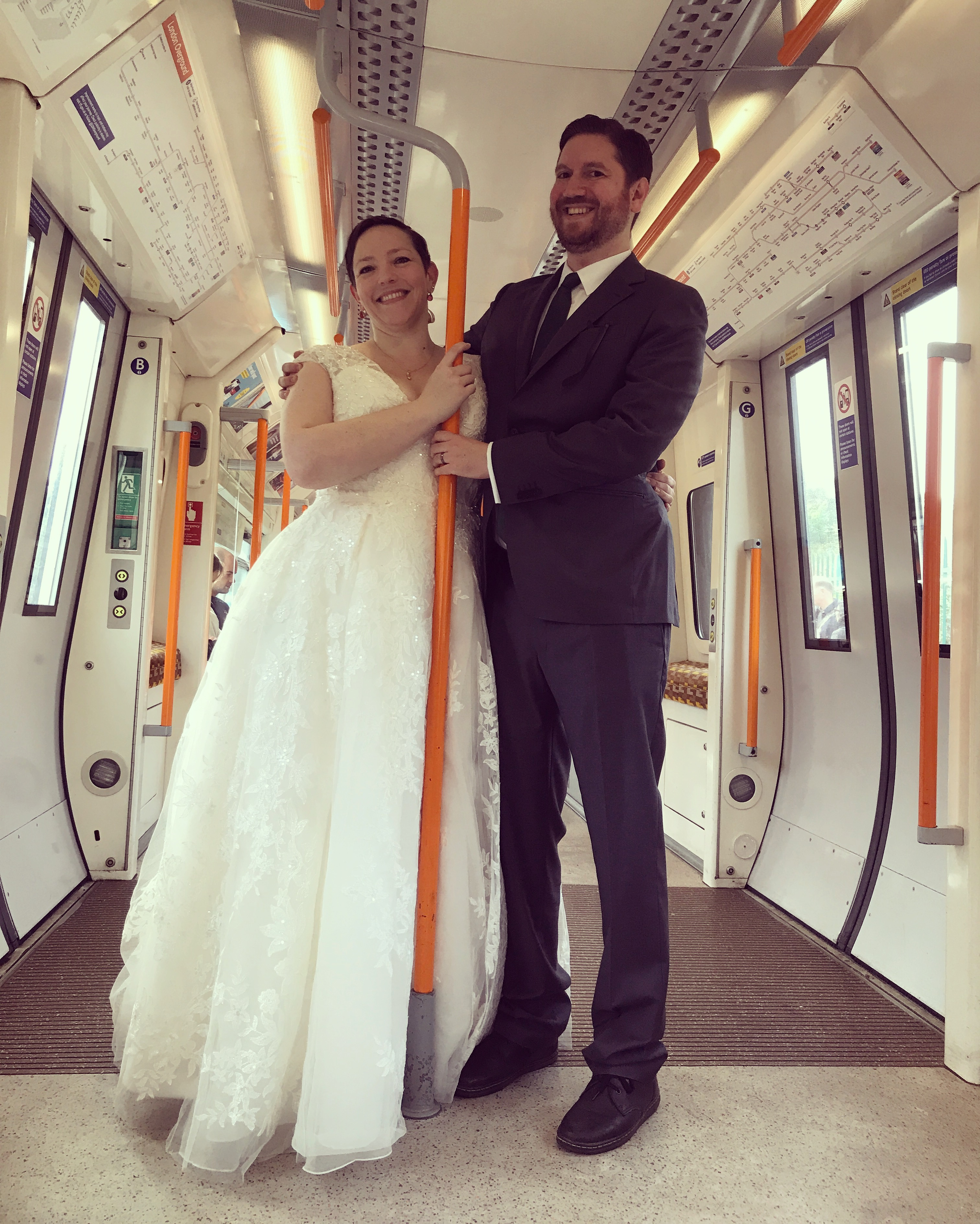 Anne and Scott on the London Overground in wedding clothes